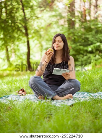 Woman using digital tablet and eating apple,  healthy lifestyle - stock photo