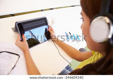 Woman Using Digital Tablet And Headphones In Design Studio - stock photo