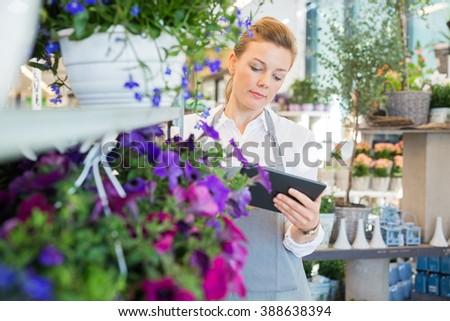 Woman Using Digital Tablet In Flower Shop - stock photo