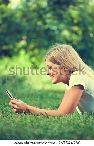 Woman using digital tablet, intentionally toned