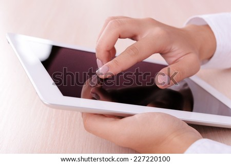 Woman using digital tablet on light background