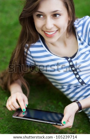 Woman using digital tablet outdoors - stock photo