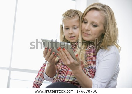 Woman using digital tablet with daughter at home - stock photo