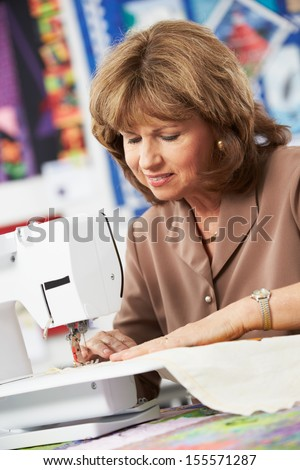 Woman Using Electric Sewing Machine