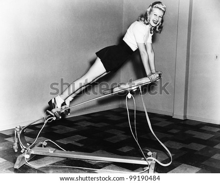 Woman using exercise equipment - stock photo