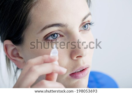 Woman using eye lotion