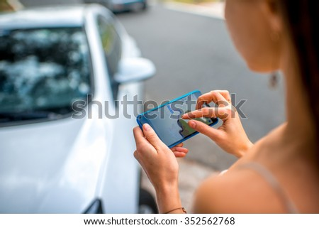 Woman using gps navigation on the smart phone near the car on the road - stock photo