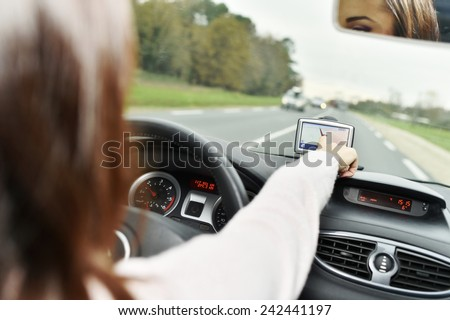 Woman using GPS while driving car