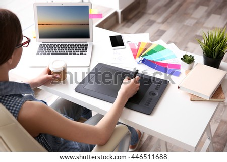 Woman using graphic tablet at office - stock photo