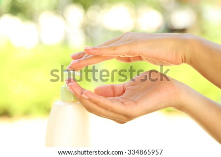 Woman using hand cream outdoors on blurred background