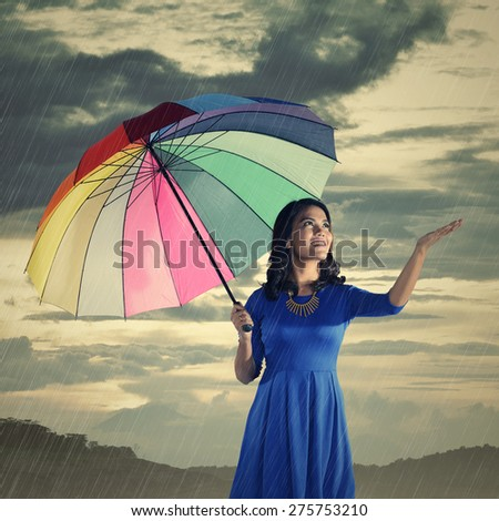 Woman using hand to know when the rain stop - stock photo