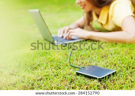 woman using hard drive disk to backup her data while lying down relaxed on a grass - stock photo