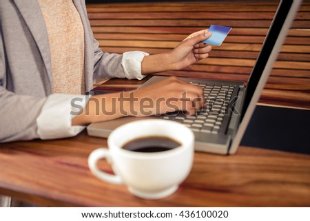 Woman using her card to buy online in a coffee shop - stock photo