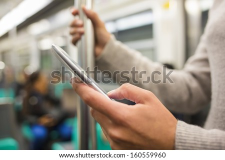 Woman using her cell phone in Subway - stock photo