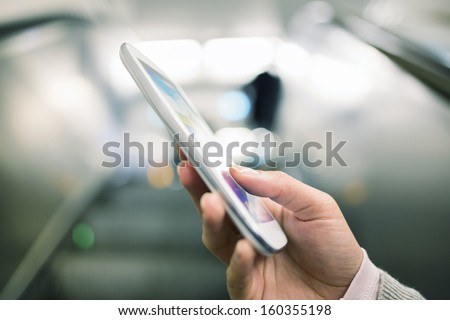 Woman using her cell phone in Subway on escalator  - stock photo