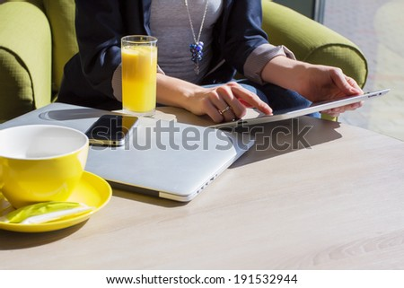 Woman using her mobile devices in cafe - stock photo