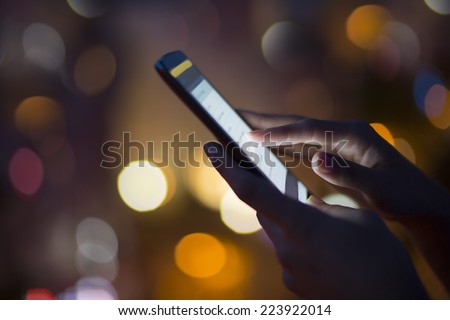 Woman using her mobile phone, city skyline night light  background - stock photo