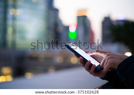 Woman using her Mobile Phone in the street - stock photo