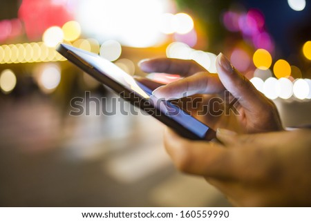 Woman using her Mobile Phone in the street, night light Background - stock photo