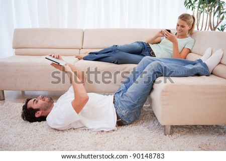 Woman using her phone while her fiance is using a tablet computer in their living room - stock photo