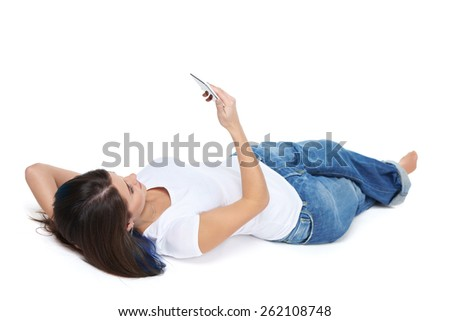 Woman using her phone while lying on her back, isolated on white background - stock photo