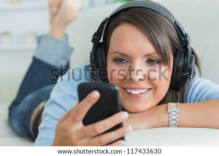 Woman using her smartphone and listening to music on sofa in the living room - stock photo