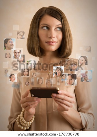 Woman using her smartphone and lots of people portraits around her. Mobile technology concept