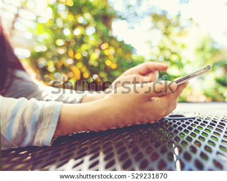 Woman using her smartphone at an outdoor cafe