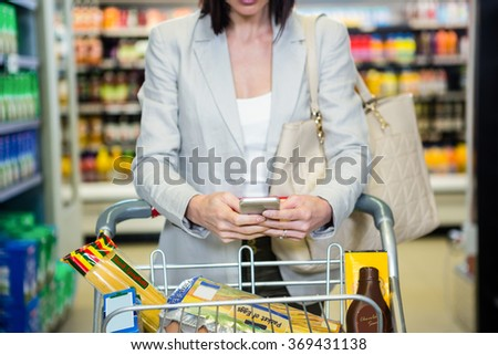 Woman using her smartphone in aisle in supermarket - stock photo