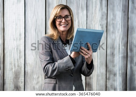 Woman using her tablet wearing a suit - stock photo