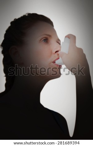 Woman using inhaler for asthma against grey vignette - stock photo