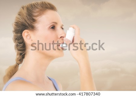 Woman using inhaler for asthma against maroon background - stock photo