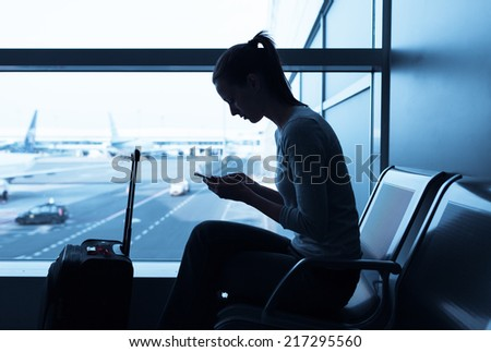 Woman using internet in the airport terminal - stock photo