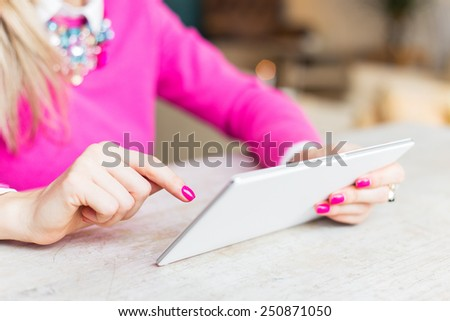 Woman using internet on tablet computer in cafe - stock photo
