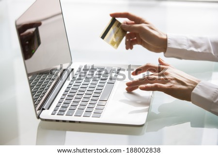 Woman using laptop and credit card.shopping online. close-up - stock photo