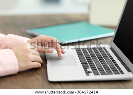 Woman using laptop at the table in office