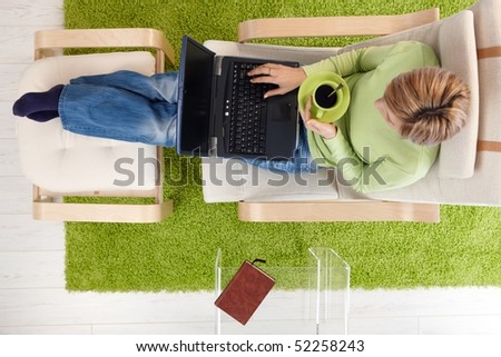 Woman using laptop, drinking coffee, sitting in armchair with legs up on footboard in overhead view.