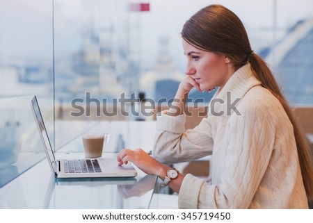 woman using laptop in modern cafe interior, free wifi, checking email - stock photo