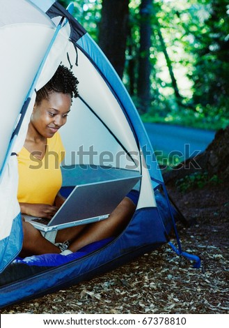 Woman using laptop in tent - stock photo
