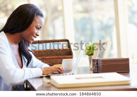 Woman Using Laptop On Desk At Home - stock photo