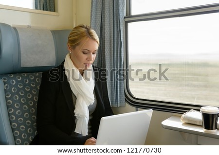 Woman using laptop traveling by train commuter serious technology reading - stock photo