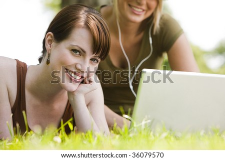 Woman using laptop while her friend listening to music - stock photo