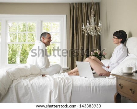 Woman using laptop while looking at man in bed