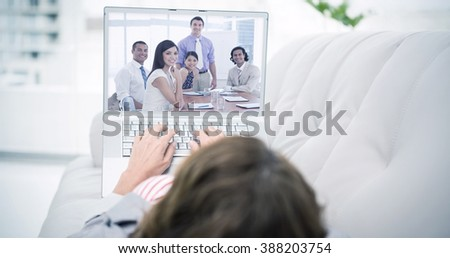Woman using laptop while lying on sofa against international business associates in a meeting - stock photo
