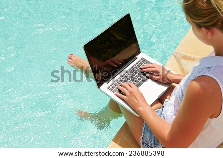 Woman Using Laptop Whilst Dangling Feet In Swimming Pool - stock photo