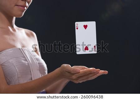 Woman using magic to make playing card levitate - stock photo