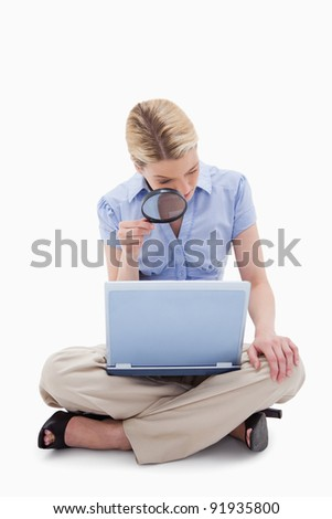 Woman using magnifier to look at her laptop against a white background - stock photo