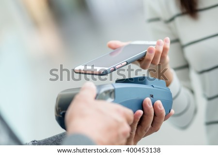 Woman using mobile phone for paying - stock photo