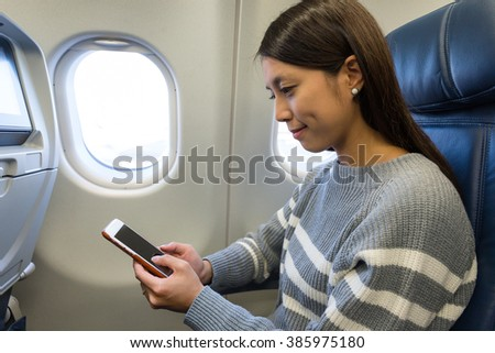 Woman using mobile phone in plane cabin