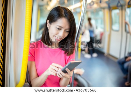 Woman using mobile phone inside train